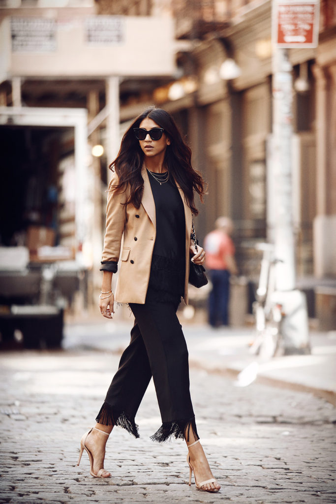 Try wearing fringed black trousers with a camel blazer for a smart yet alternative look. Via Kayla Seah.  Blazer: Rag & Bone, Top: CMEO, Trousers: Anna Quan, Bag: Chanel.