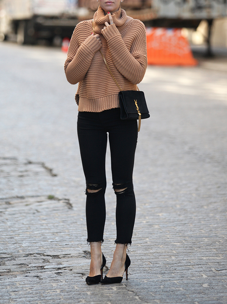 Helena Glazer wears a pair of distressed black jeans with a knitted camel pullover. Coat: Vince, Sweater: C/Meo, Jeans: Express, Shoes: Marc Fisher.