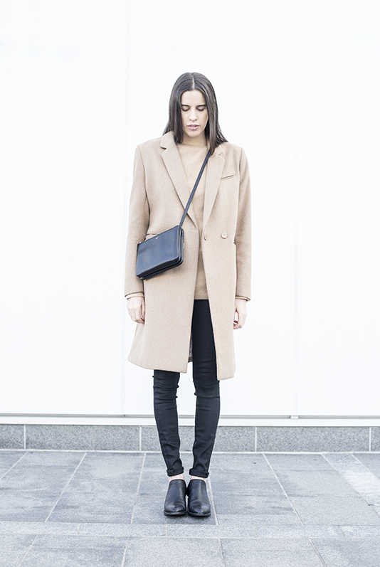 Melissa Araujo is wearing a camel coat from H&M, camel cashmere sweater from Splendid, black jeans from J Brand, black boots from Alexander Wang and the bag is form Celine