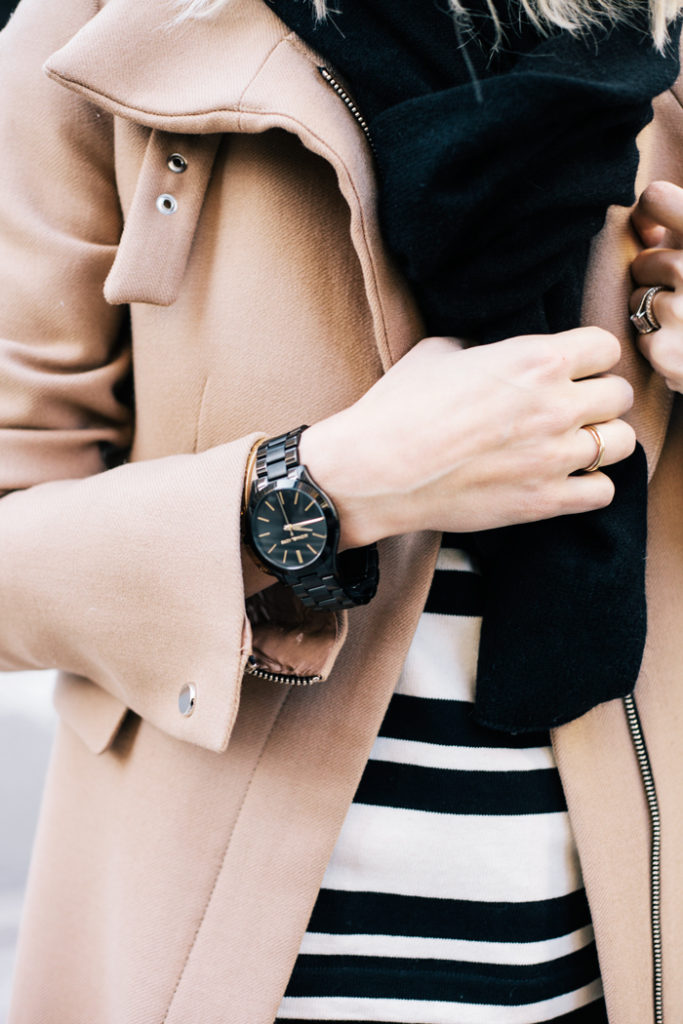 Jacey Duprie is wearing a camel and black outfit, down to the watch which is from Michael Kors