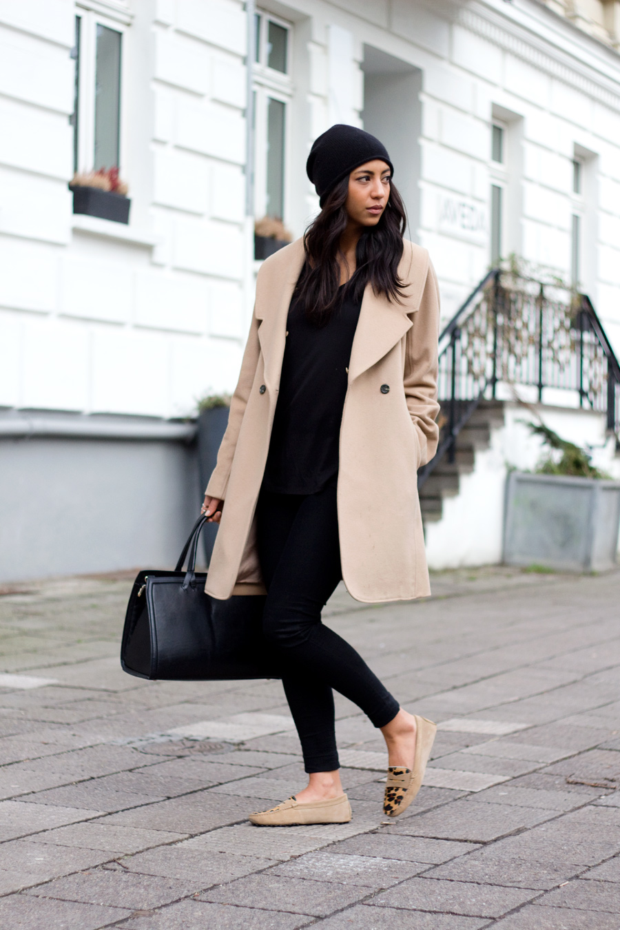 Camel And Black: Kayla Seah is wearing a camel coat from Club Monaco, black top from Alexander Wang, black jeans from J Brand, camel shoes from Bobbies Paris, black beanie from Cos and the bag is from Zara