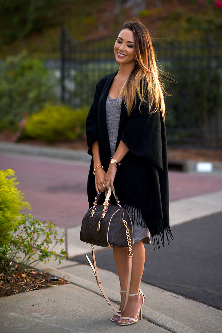 Jessica R. is wearing fringed black blanket coat with cream heels. Cardigan, Watch, Earrings: Ross, Bag: Michael Kors.