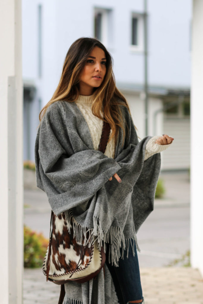 Consuelo Paloma wears a gorgeous grey poncho from Ralph Lauren.   Poncho/Bag: Ralph Lauren, Jeans: H&M.