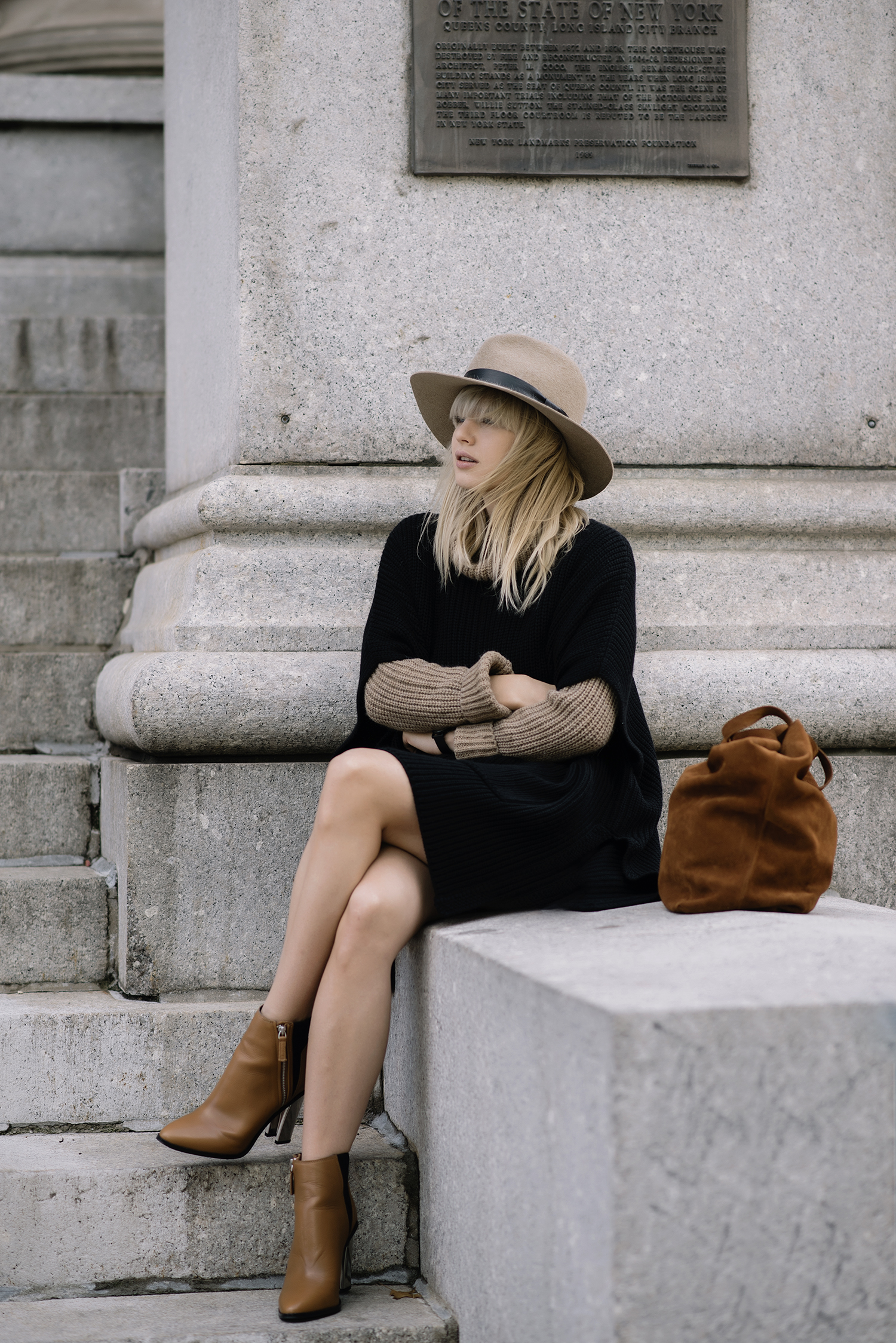 Lisa Dengler wears an oversized black poncho over a beige knit, paired with a matching hat. Boots: Aldo, Poncho: Aritzia, Turtleneck: Tommy Hilfiger.