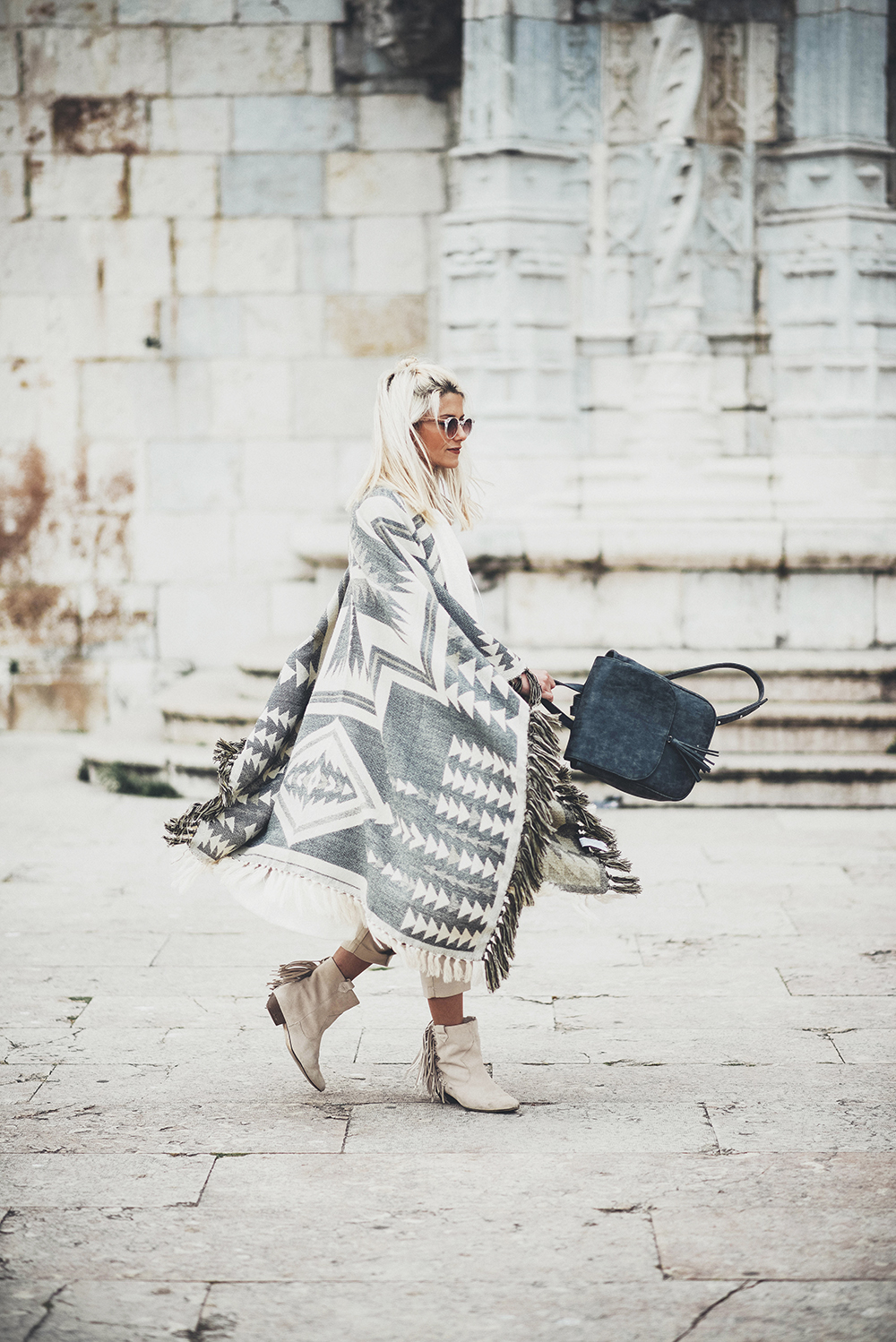 An Aztec style poncho is the ultimate festival must-have. Barbara Ines is looking super bohemian in this oversized grey and white piece, worn with cowboy style frayed boots and a leather satchel. We love this look! Poncho: Berskha, Bag: Mariosca, Boots: Zara.
