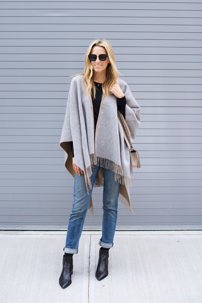 Try pairing your poncho with boyfriend jeans and patent black ankle boots for a simple but sophisticated look. Via Lisa D Cahue.  Jeans: Rag & Bone, Boots: Acne Studios.