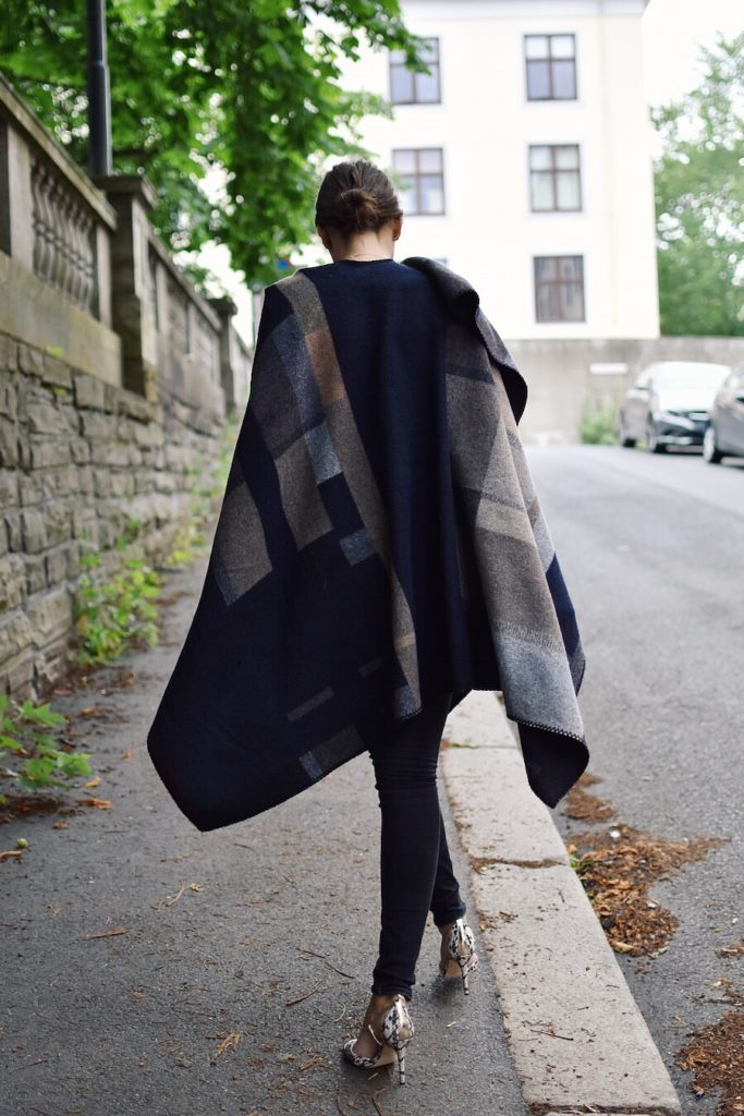 Darja Barannik wears her poncho over black skinny jeans, and finishes the look with a pair of patterned heels.   Poncho: Holzweiler, Jeans: Tiger of Sweeden, Shooes: Jimmy Choo.