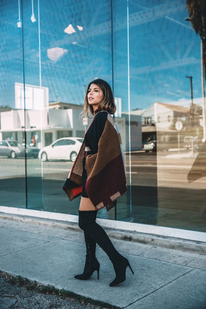 The blanket coat trend has never been hotter than it is right now! Pam Hetlinger has paired this block print piece with thigh high black boots for a sexy and sophisticated style which we adore!   Coat: Burberry.