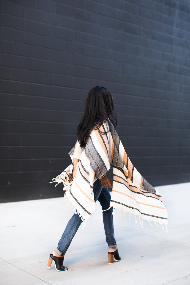 Poncho Cape Trend: Sheryl Luke is wearing a lightweight stripe open poncho from Urban Outfitters