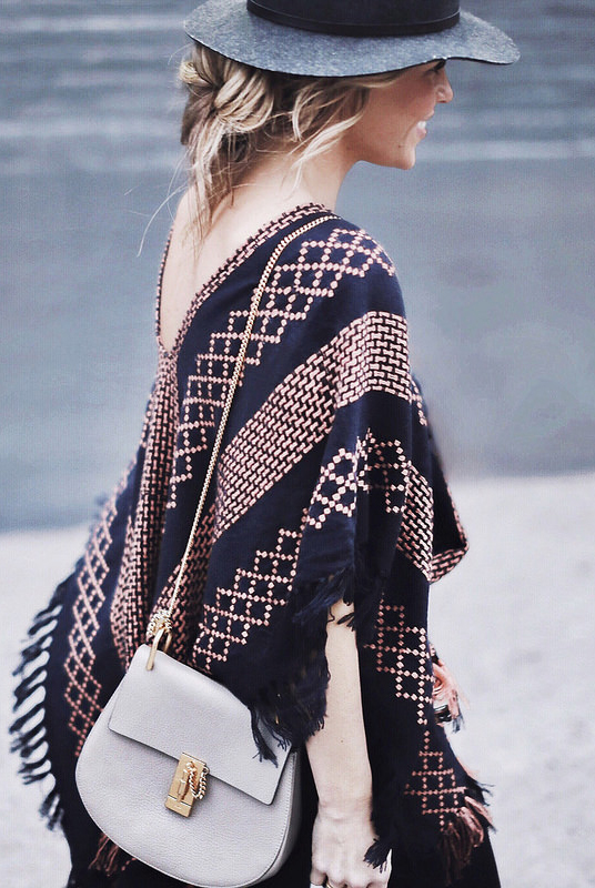 Mary Seng is wearing a black and camel poncho from Free People