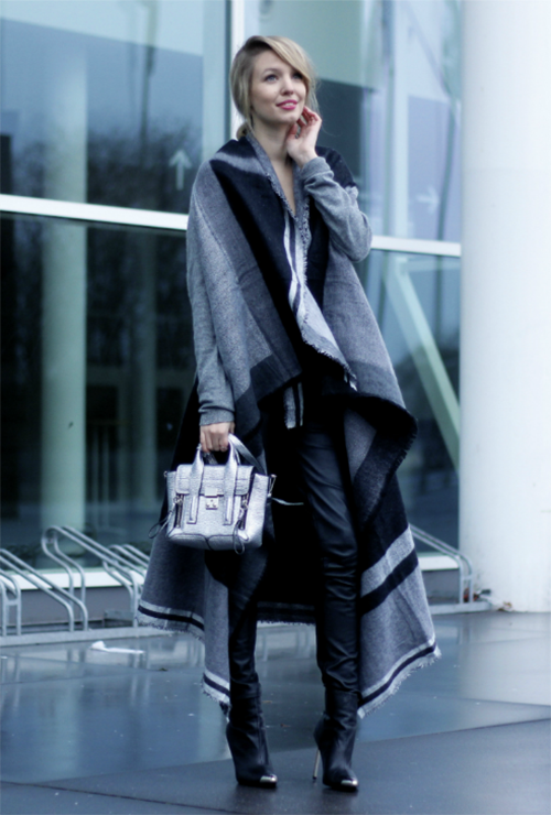 Leonie Sophie is wearing a grey and black long poncho from Zara