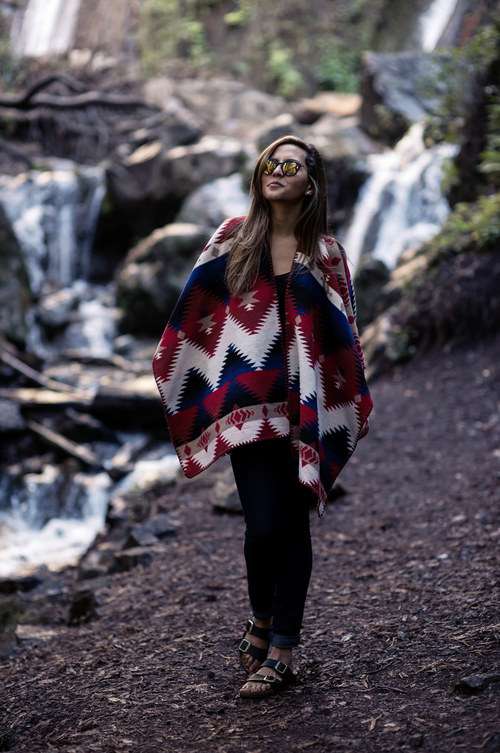 Raquel Paiva is wearing a blue, red and white poncho from Forever 21