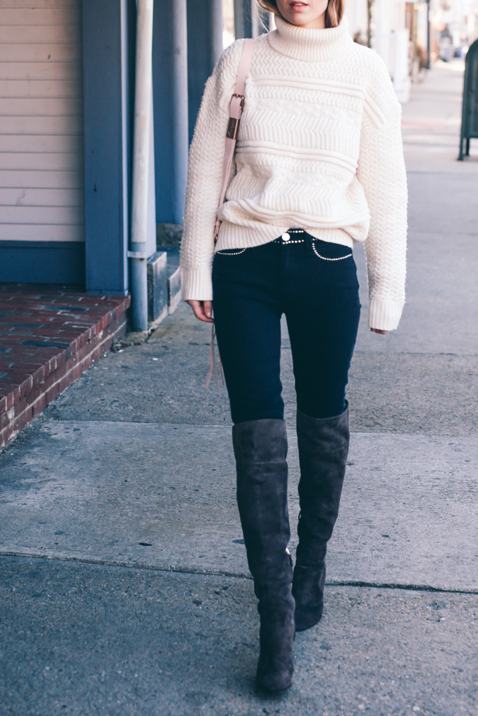 Jess Ann Kirby is preparing for spring in this blush pink cable knit rollneck, paired with skinny denim jeans and over the knee boots. Knit: Reiss, Jeans: Paige Denim, Boots: L.K. Bennett.