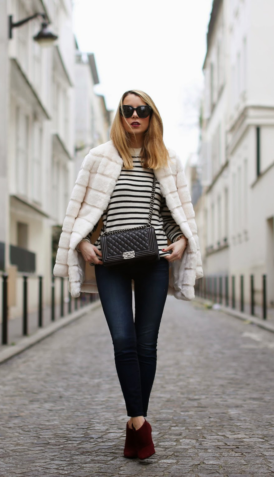 Caroline Louis is wearing a white faux fur coat and burgundy boots from Zara, jeans from Talley NYC, striped knit sweater from &Otherstories and the bag is from Chanel