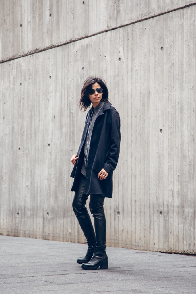Crystal Yeoms is wearing a grey button up shirt from Acne Studios, black coat from A.P.C, leather trousers from H&M and platforms from Vagabond