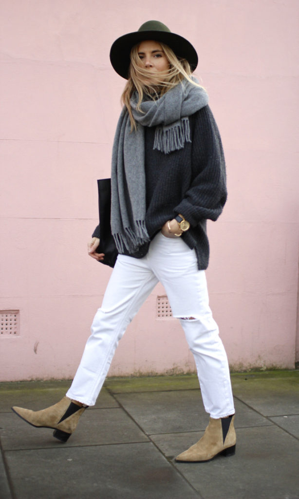 Lucy Williams is wearing distressed white pop jeans, grey scarf and camel boots from Acne, dark grey knit top from Theory, hat from Revolve and the bag is from Zara