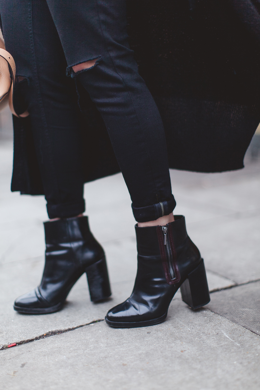 Carrie Harwood is wearing black ankle boots with a burgundy zipper from Zara