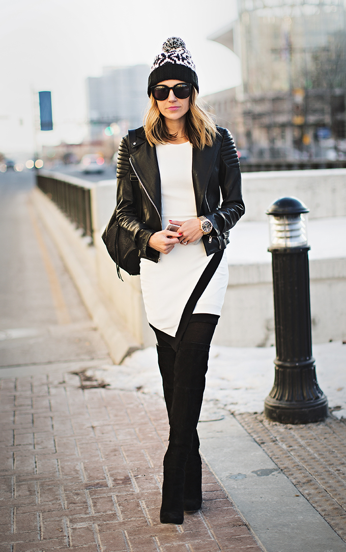 Street Style: Christine Andrew is wearing a black and white dress from Lulu's, black leather moto jacket from A.L.C, beanie from Old Navy and black over the knee boots from Sam Edelman