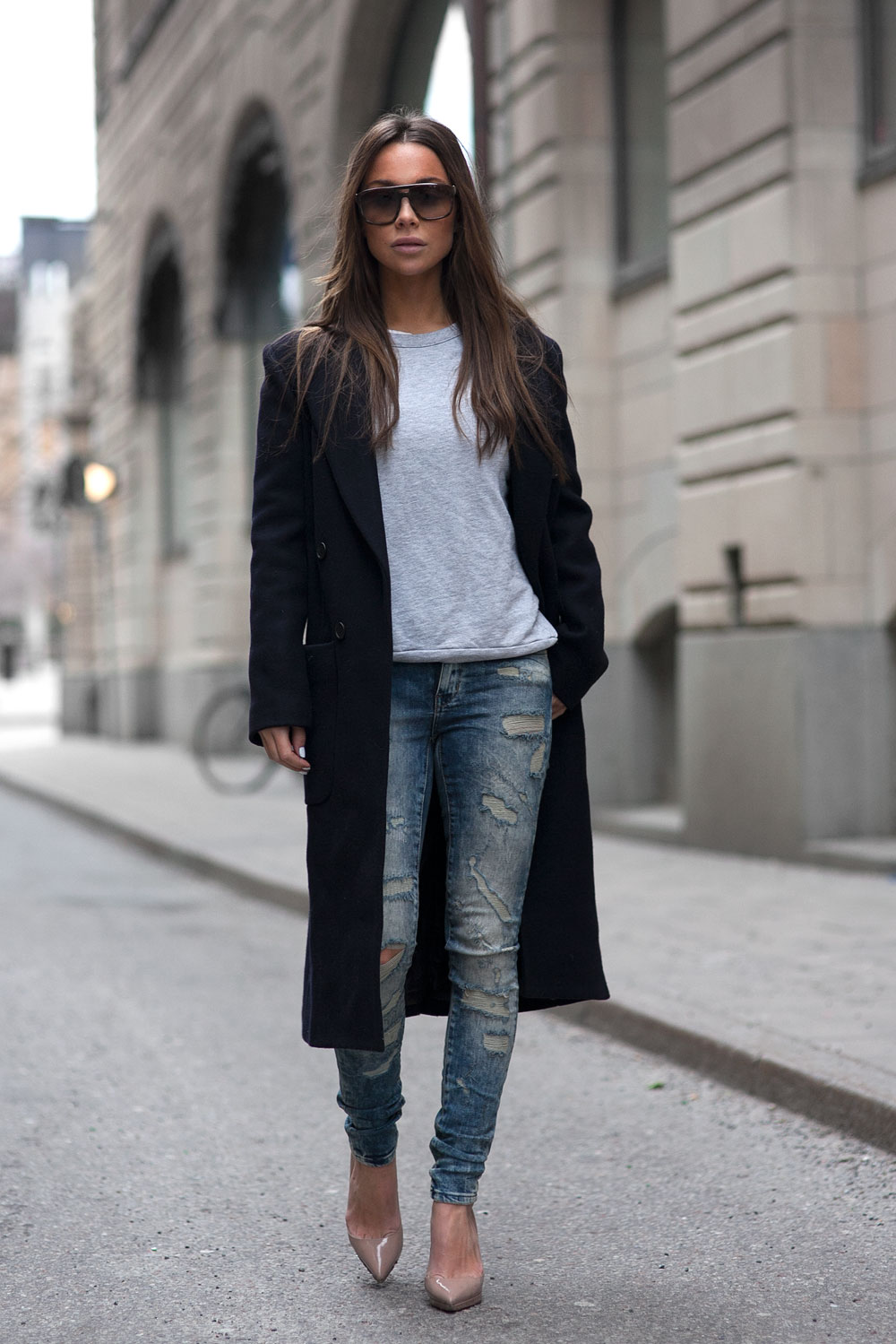 Johanna Olsson is wearing ripped blue jeans from Noisy May, nude shoes from Christian Loboutin and the black coat is from LXLS