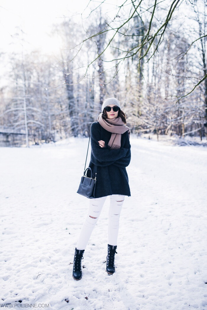 Paulien Riemis is wearing an oversized dark grey sweater from H&M, white ripped jeans from Blanco Suite, scarf from American Vintage, the bag is from Coach and the boots are from Polette