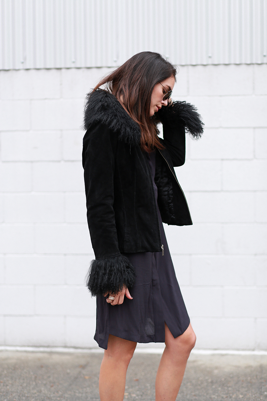 Brittany Xavier is wearing a black shirt dress from H&M and a black fur trimmed vintage jacket