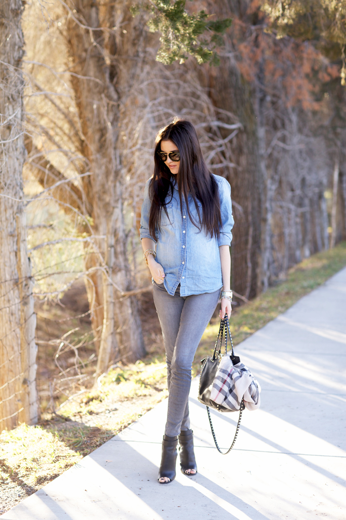 Rachel Parcell is wearing a a denim shirt and grey jeans from J.Crew, the bag is from Valentino, the sunglasses from Prada and the boots are from Vince