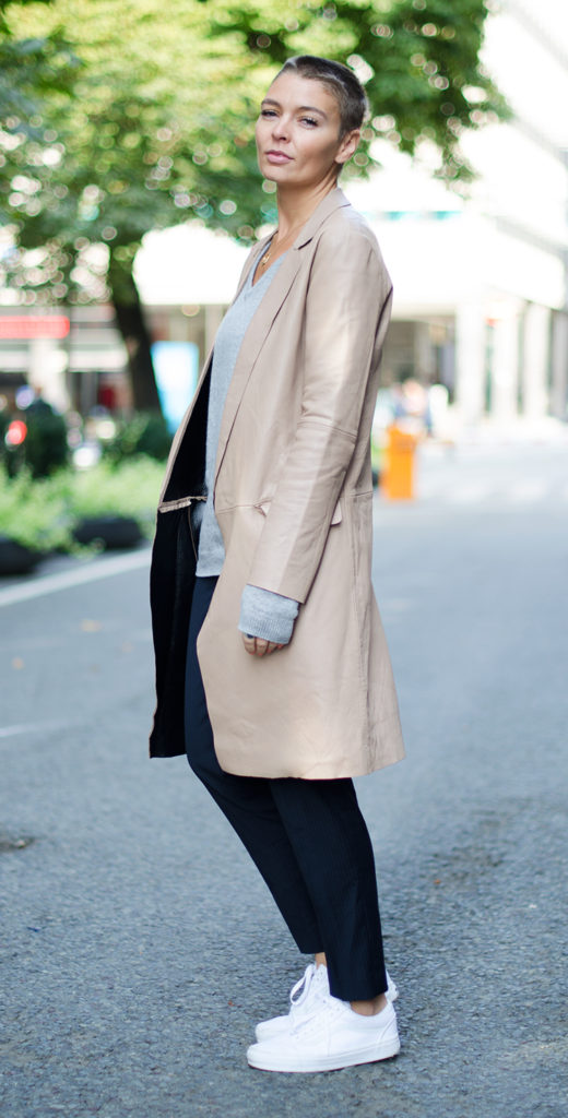 Marie Ullevoldsater is wearing black suit trousers and grey V-neck from MQ, sneakers from Vans and the leather trench coat is from Zara