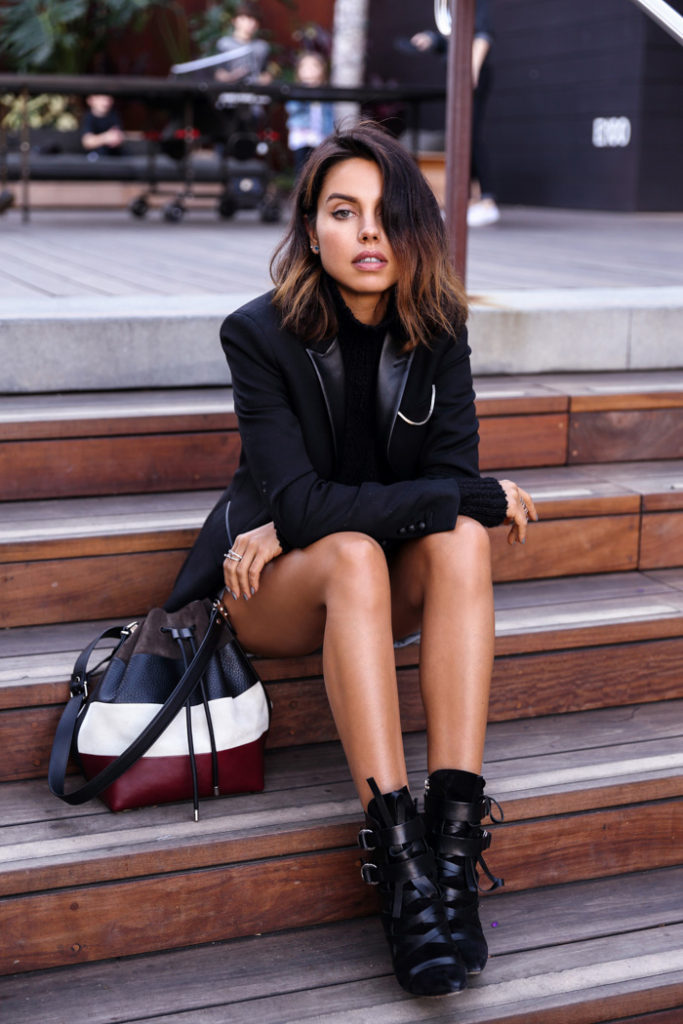 Annabelle Fleur is wearing a medium sized bucket bag from Proenza Schouler, black blazer from The Kooples, buckle boots from Isabel Marant and the turtleneck is from Banana Republic