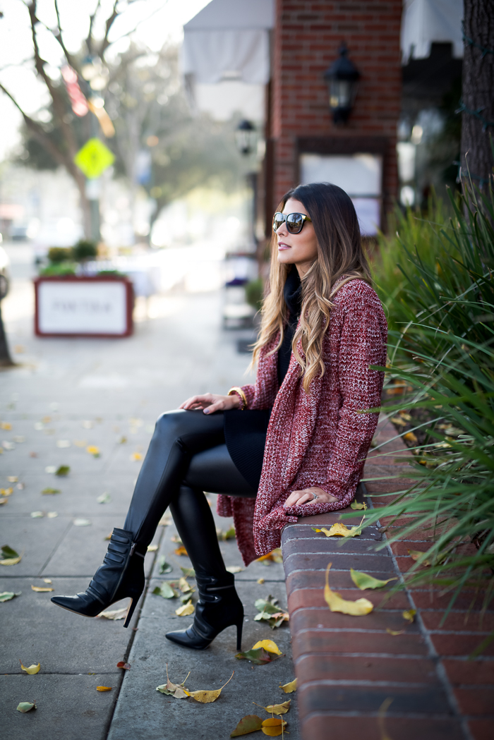 Pam Hetlinger is wearing a black turtleneck Dress from Banana Republic, black faux leather leggings from Topshop, red shawl cardigan from Saylor Clothing and the booties are from Sam Edelman
