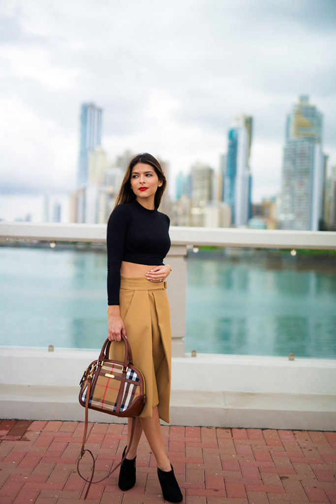 Pam Hetlinger is wearing camel double buckle skirt from Zara and a black long sleeves crop top from Asos