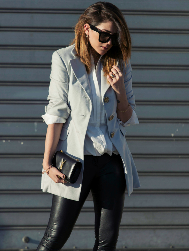 Nicoletta Reggio is wearing a grey blazer from Gianfranco Ferrè, white shirt from H&M, black leather trousers from VentyFive and the bag is from Saint Laurent