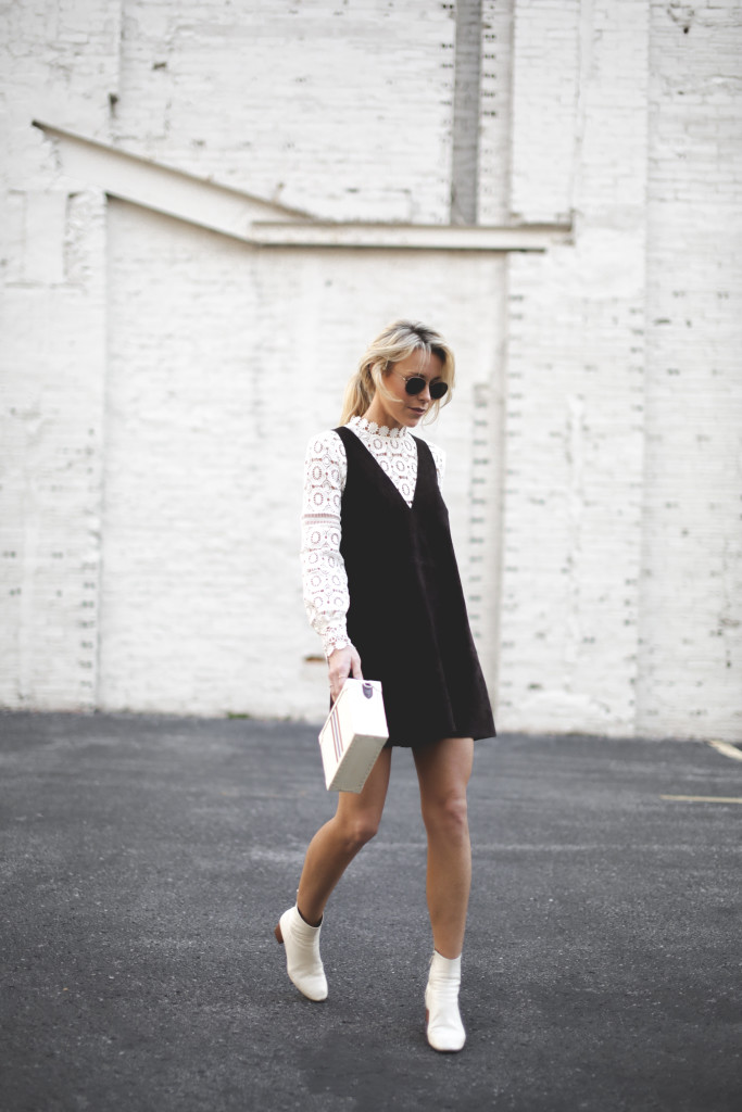 The suede dress trend is absolutely upon us this season! Mary Seng is wearing the look as part of a minimalistic and understated look, consisting of a suede V neck pinafore worn over a lace top with white Chelsea boots. Dress: Free People, Top: Self Portrait, Boots: Isabel Marant.