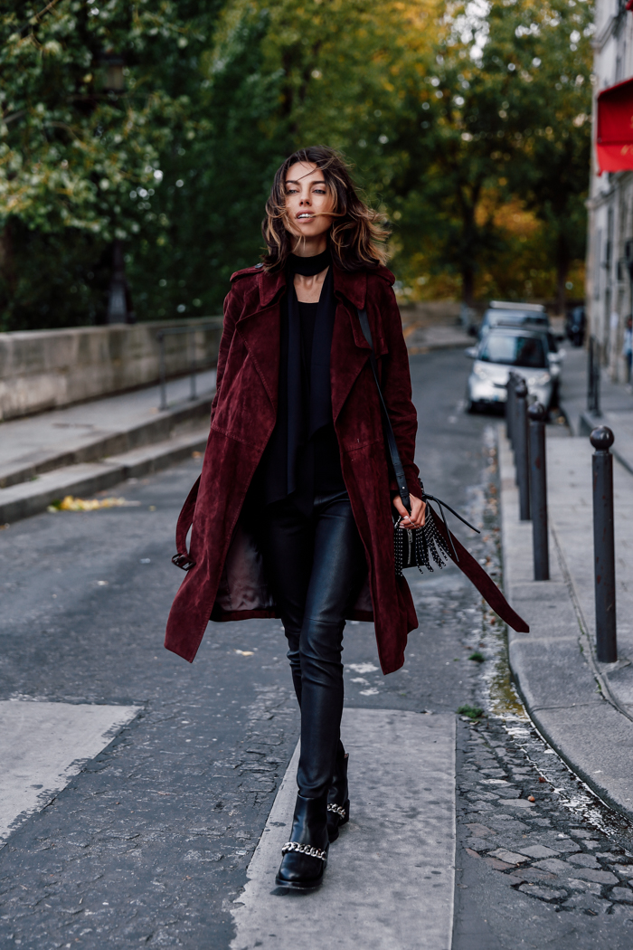 Annabelle Fleur wears a crimson suede trench coat with leather trousers and studded ankle boots with a matching bag. Coat: Diane Von Furstenburg, Leather Trousers: J. Brand.