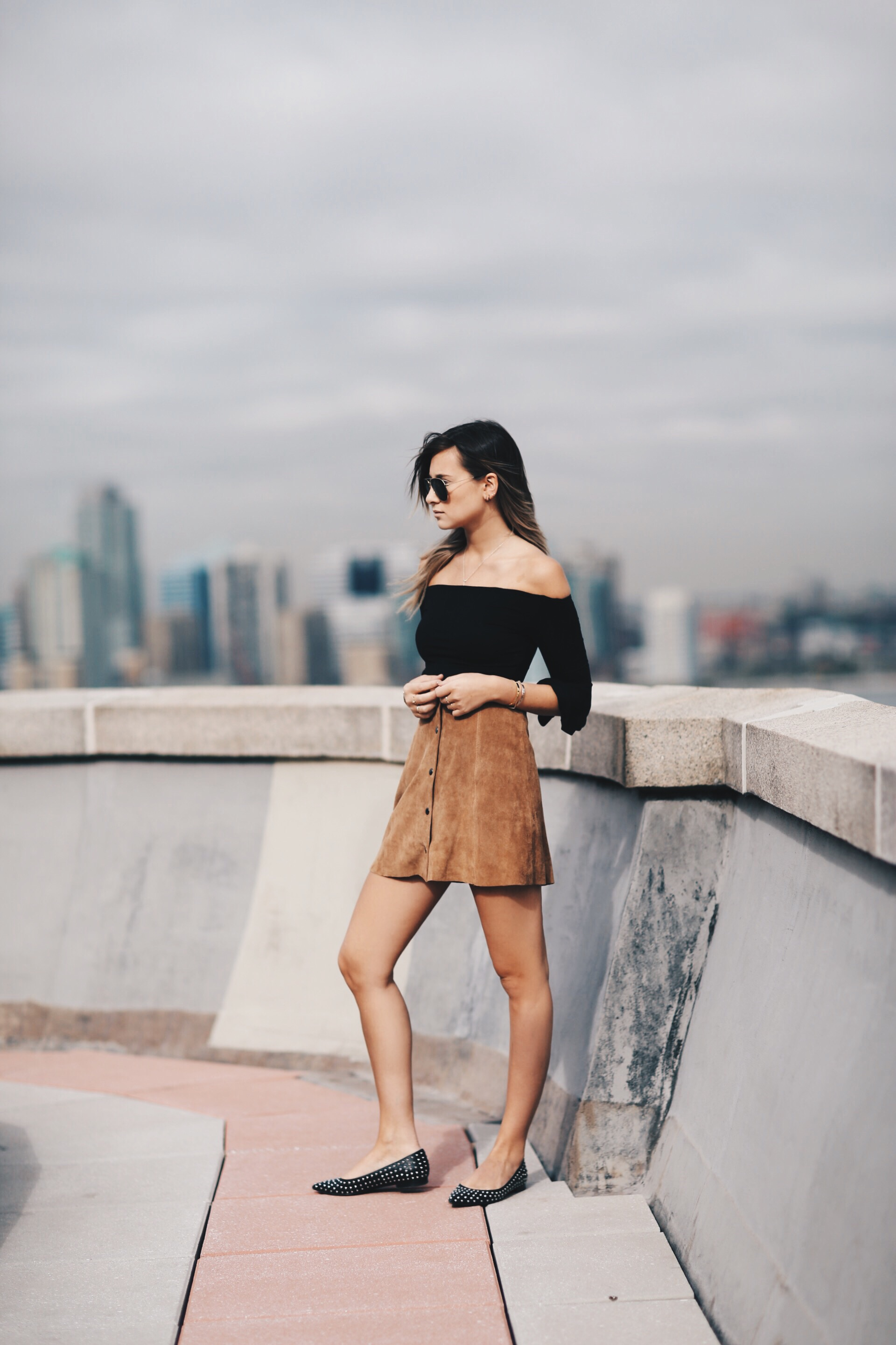 Danielle Bernstein is wearing a black off the shoulder top and a suede skirt both from Topshop
