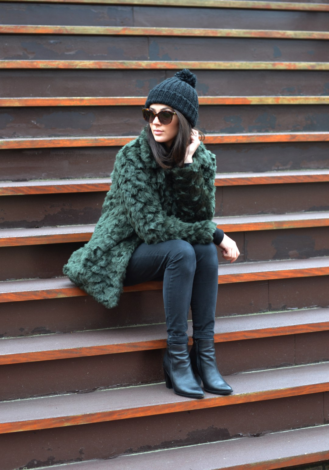 Try wearing the faux fur trend oversized to get those extra cosy winter vibes. Mary Josephine wears an emerald green coat with skinny black jeans and a matching beanie; a classic winter look. Sweater: Brandy & Melville, Jeans: River Island, Beanie: Primark, Boots: Sacha, Sunglasses: Fendi.