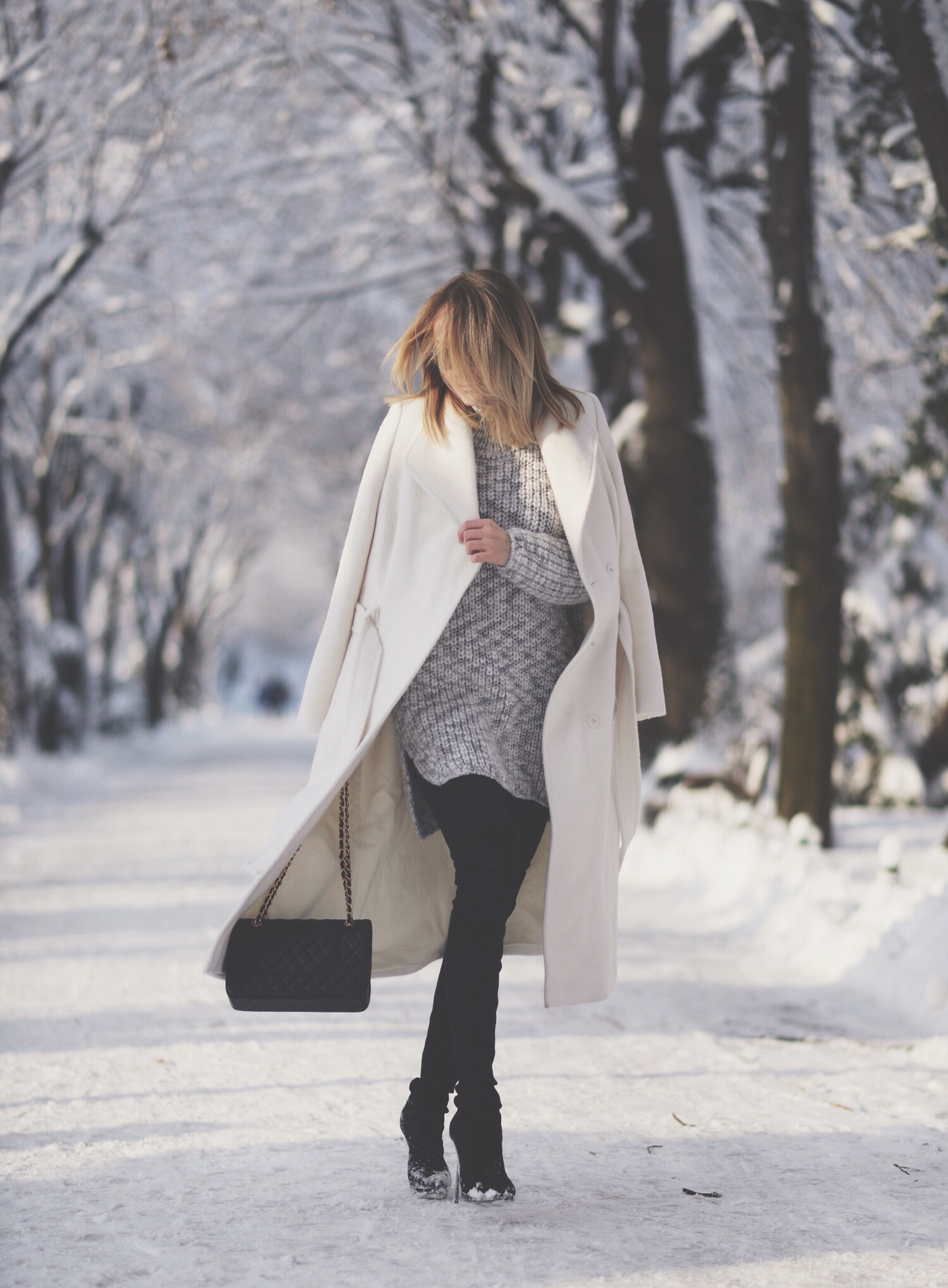 Winter Outfit Ideas: Silvia Postolatiev is wearing a white long coat from Marks & Spencer, grey knit top from Zara, black over the knee boots from Casadei, bag from Chanel and the black jeans are from Mango