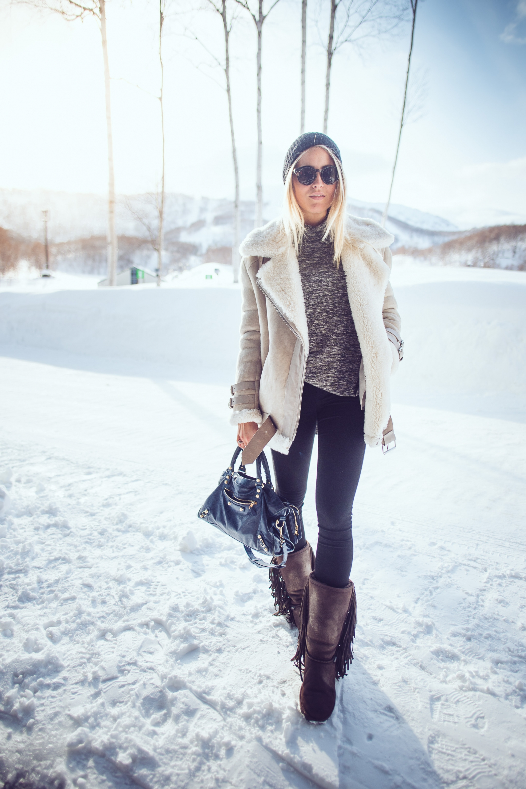 Janni Deler is wearing a shearling coat from Acne, grey top and sunglasses from Lindex, jeans from Nelly, bag from Balenciaga and the boots are from Warmbat