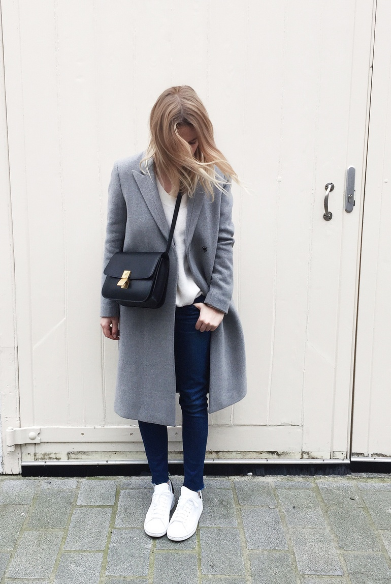 Mirjam Flatau is wearing a light grey melange coat from Filippa K, wote cashmere jumper from Fine Collection, bag from Celine, ripped jeans from A.N.D and the sneakers are from Adidas