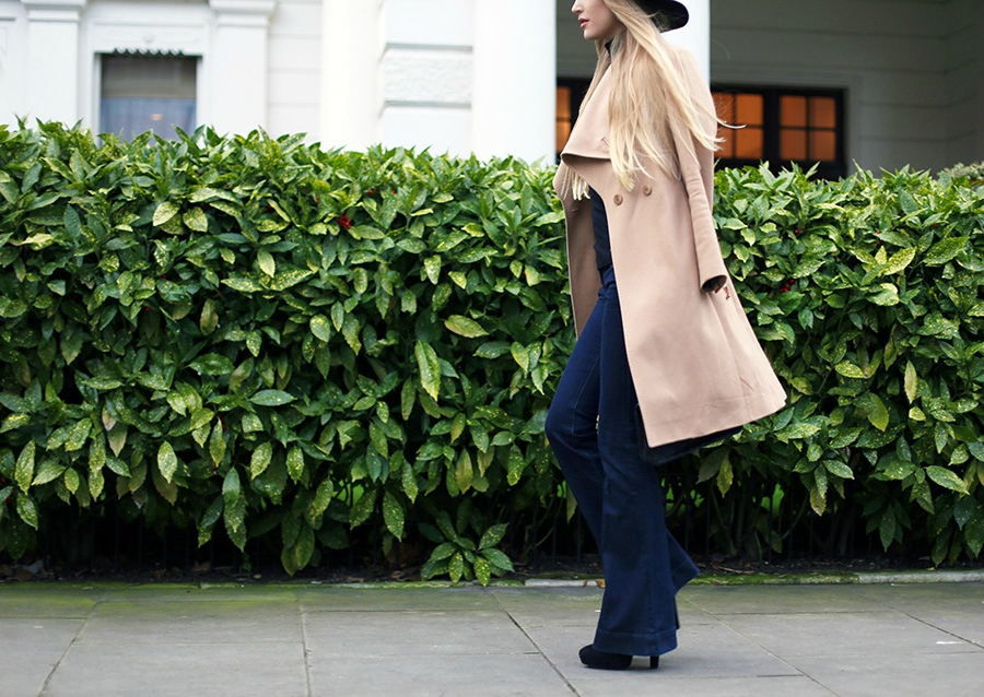 70's Fashion Trend: Celina is wearing a pair of denim flare jeans with a camel Ted Baker coat