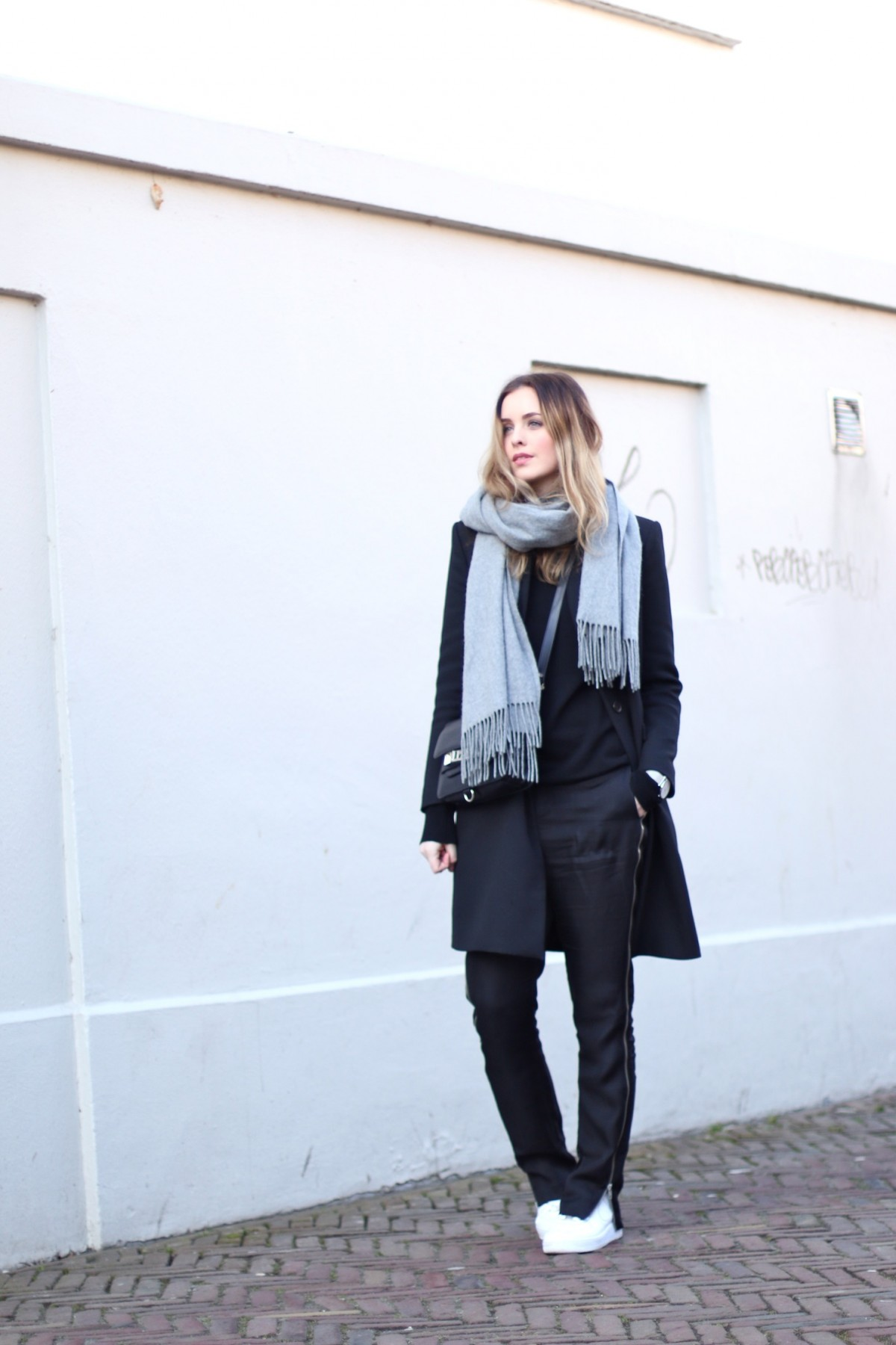 Roos-Anne van Dorsten is wearing a pair of black Nowhere trousers, a coat from Zara and a grey Weekday scarf