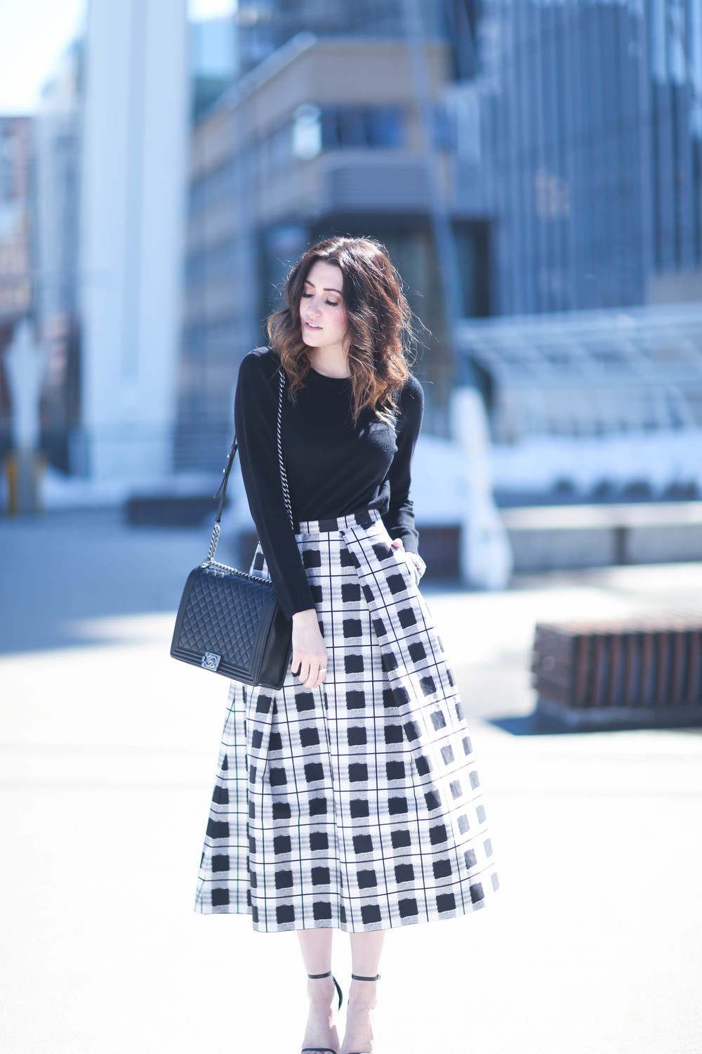 Black and White Outfit Ideas: Hailey Middleton is wearing a black long sleeved Rag & Bone sweater with a plaid mid length skirt