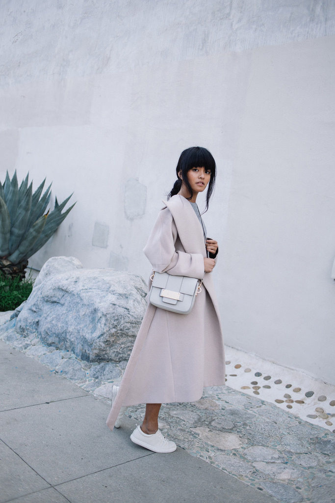 Olivia Lopez is wearing a Reformation coat with white Dolce Vita sneakers
