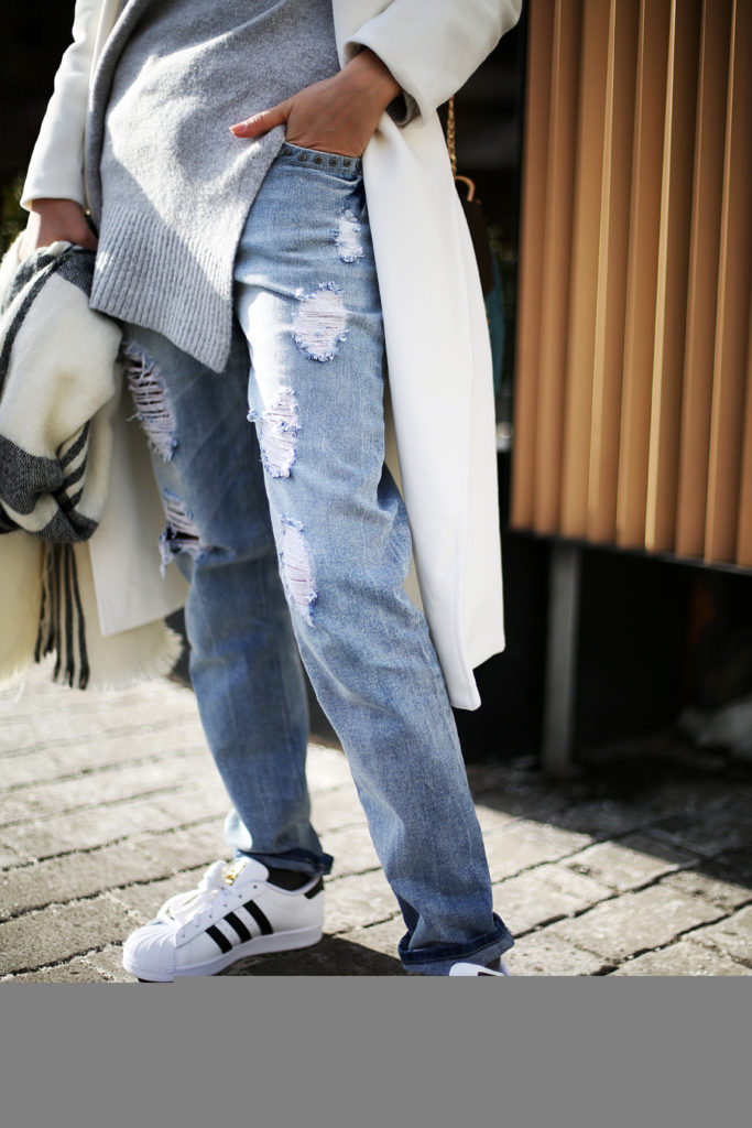 Tina Sizonova is wearing a pair of denim ripped jeans with a creme coat and Adidas superstars
