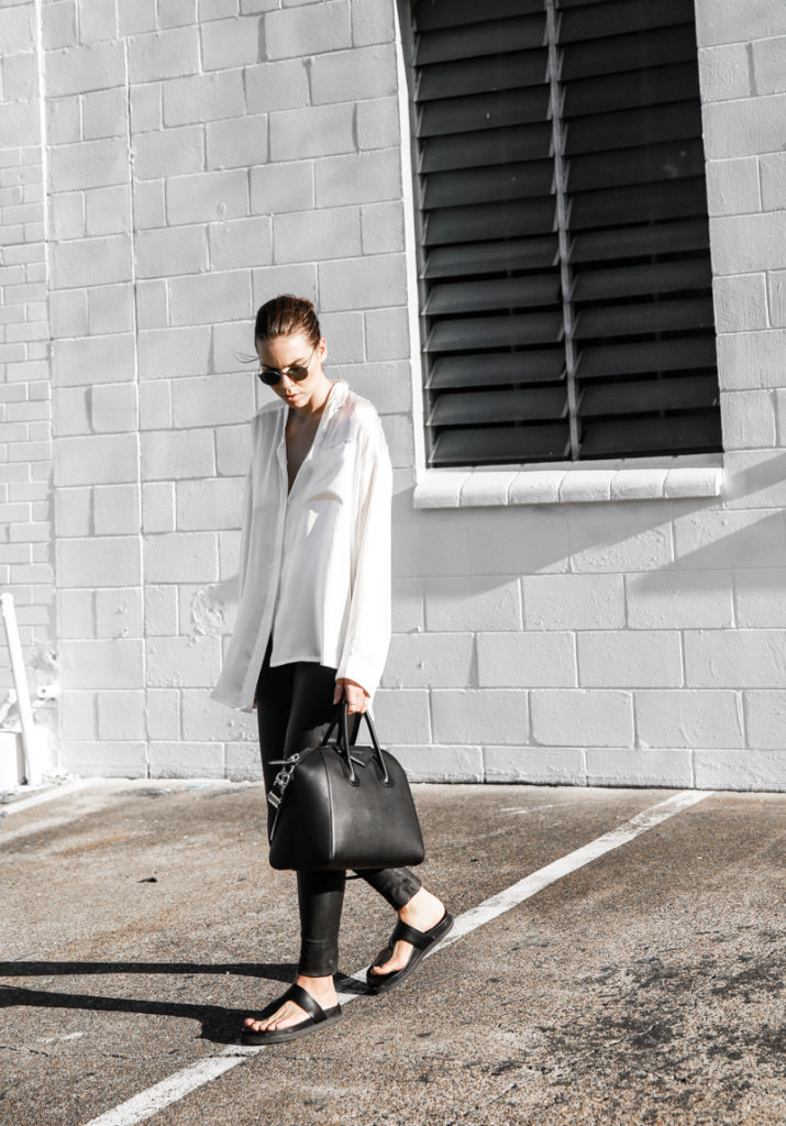 Black And White Outfit Ideas: Kaitlyn Ham is wearing an Asos white loose shirt with Helmut Lang leather pants and black chunky sandals