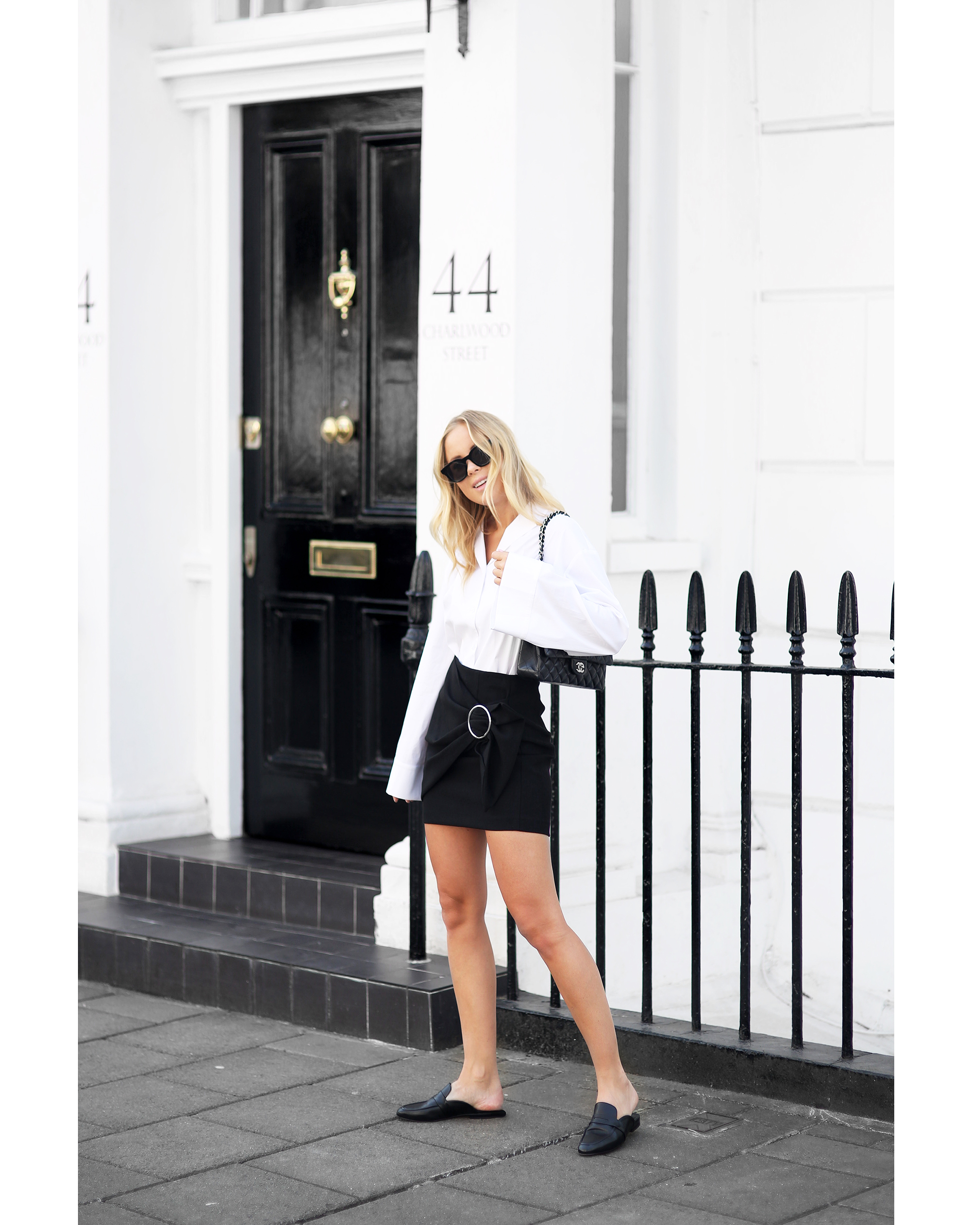 Victoria Tornegren is looking ultra sleek in this black and white outfit consisting of a bow front skirt with metallic detailing and a bell sleeved white blouse. This style is sophisticated yet playful; perfect for sprucing up your work wardrobe! Bag: Chanel, Shirt: Front Row Shop, Loafers: Henry Kole, Skirt: Zara.