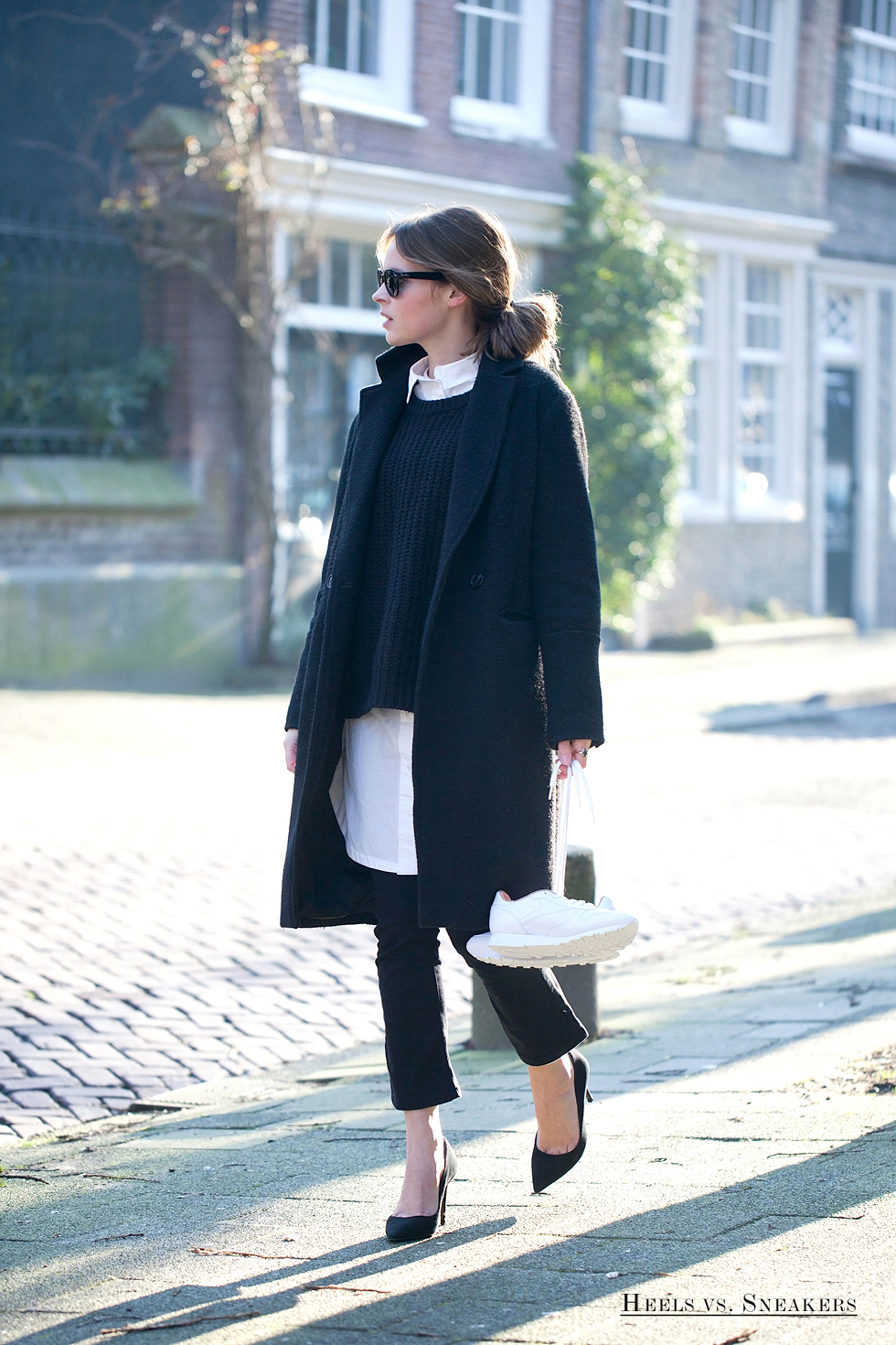 Christine R. is showing us how to wear the black and white trend, creating an ultra sophisticated look by pairing a white shirt with navy knitwear and a smart matching overcoat. Coat/Shirt: H&M, Sweater: Ganni, Jeans: BDG, Shoes: Tamara Mellon.