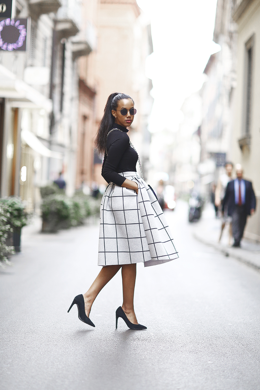 Josefin Dahlberg wears a statement patterned skirt with a plain black roll neck top and heels. Skirt/Shoes: Topshop, Top H&M, Bag: Mango, Sunglasses: Åhlens.