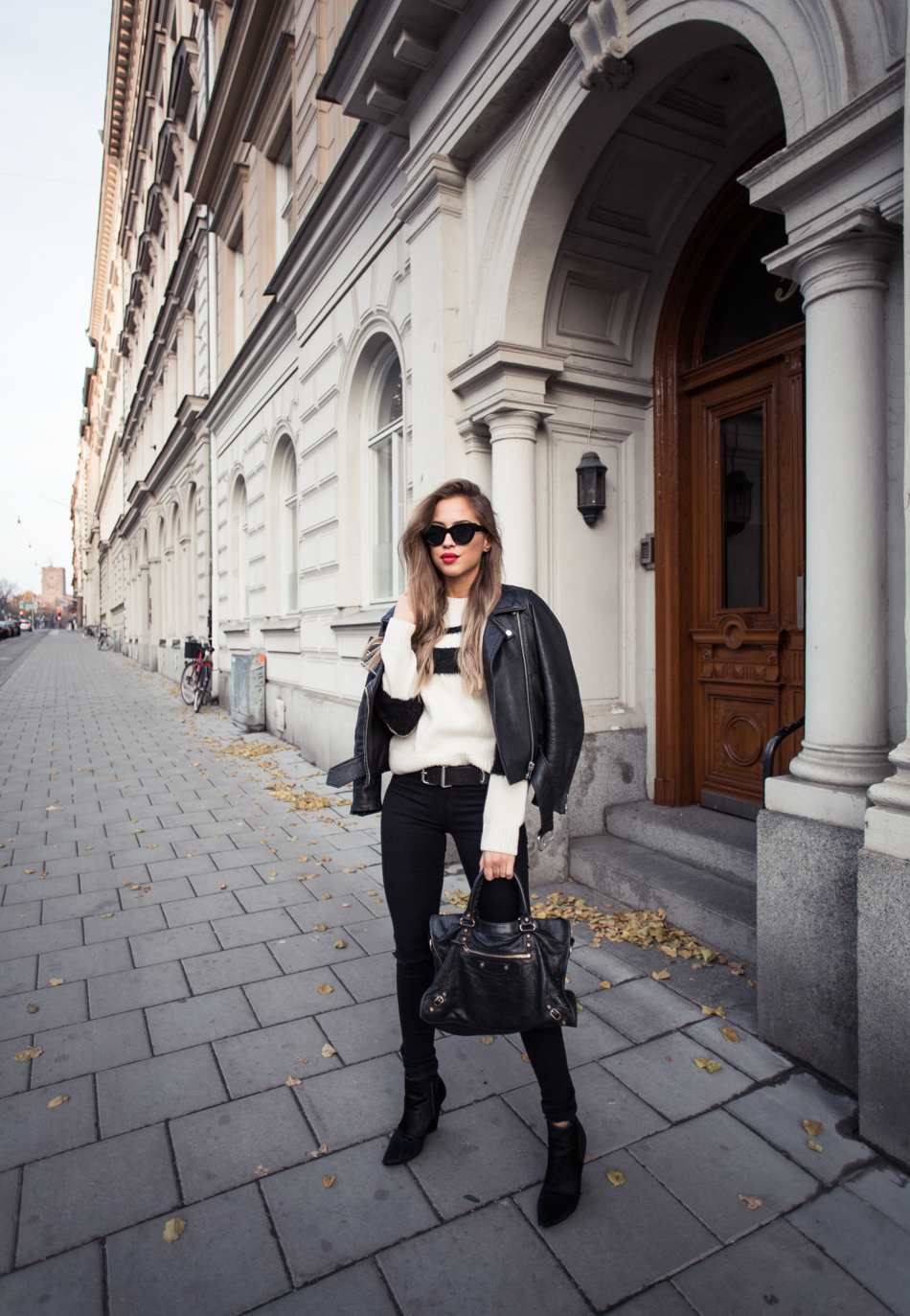 Kenza Zouiten looks ultra sleek in skinny jeans, a striped black and white sweater, and a stylish leather jacket. Sweater: Anine Bing, Jeans: Serious Sally, Boots: Jennie-Ellen, Bag: Balenciaga.