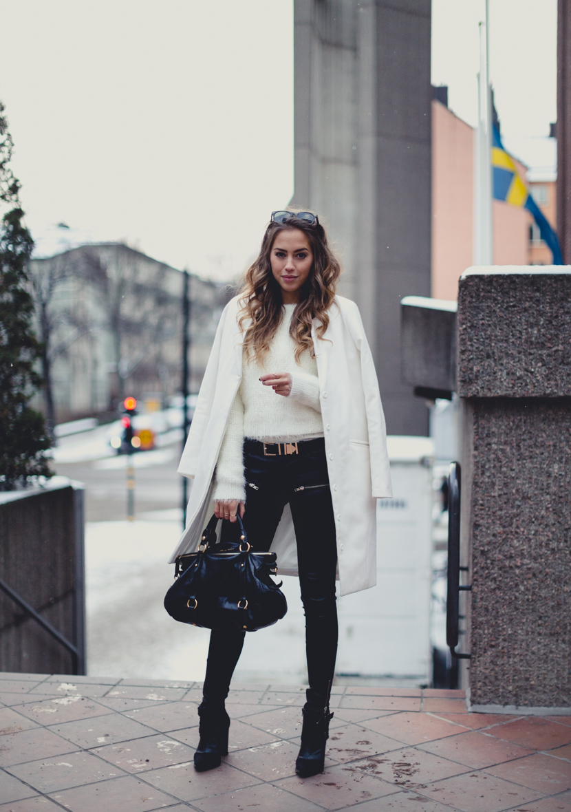 Black And White Only Outfits: Kenza Zouiten is wearing black leather trousers from Jofama by Kenza, white sweater from Forever 21, the bag is from Miu Miu bag, and the black ankle boots and the white coat is from Notion 1.3