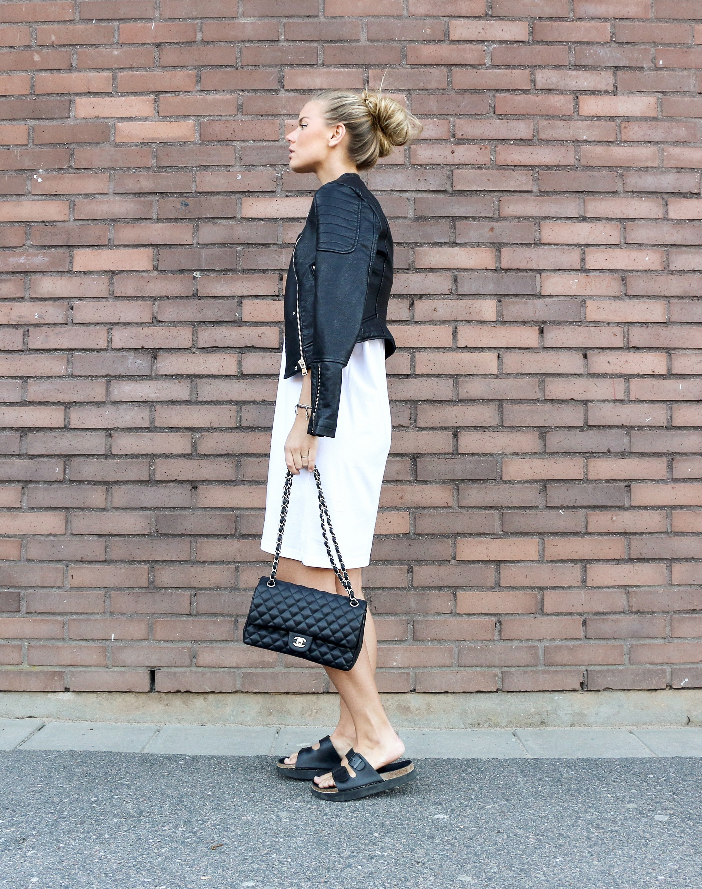 Frida Grahn is wearing a white T-shirt dress, black leather jacket, sandals and bag Sandals: Din Sko, Bag: Chanel, Leather Jacket: Chiquelle, T-shirt dress: H&M